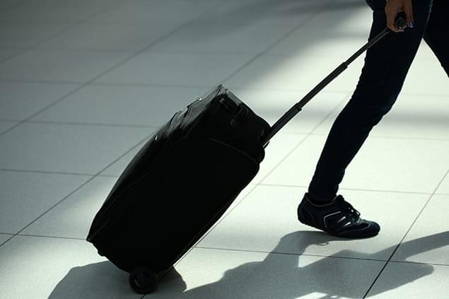 Image of a person dragging a suitcase